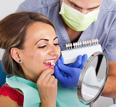 woman in red shirt trying on porcelain veneers in dental chair