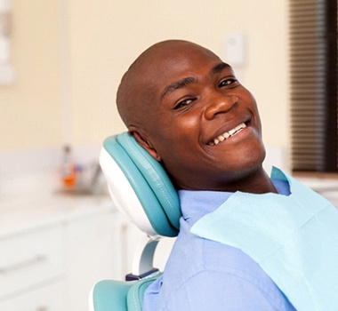 A smiling man visiting the dentist for a checkup.
