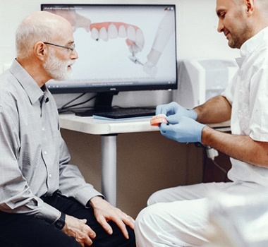 Dentist showing a patient a model denture.