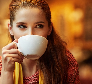 A woman drinking from a mug.