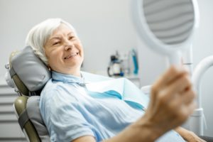 person looking at their dental implants in the mirror