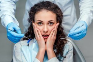 Woman with loose tooth visiting her Landrum emergency dentist